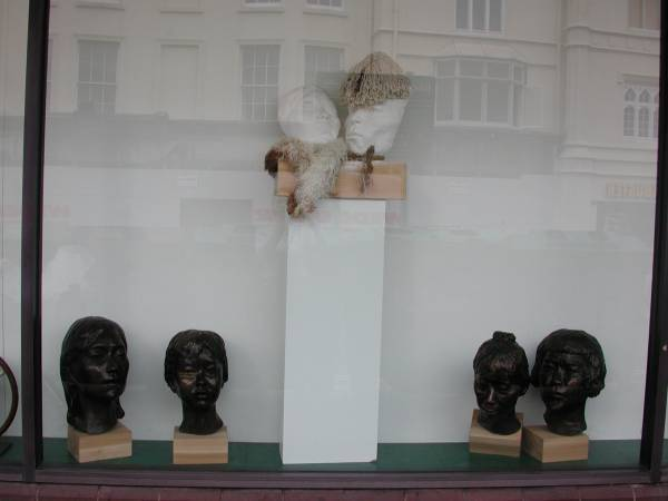 Middle section of window in gallery showing sculptures by Laury Dizengremel