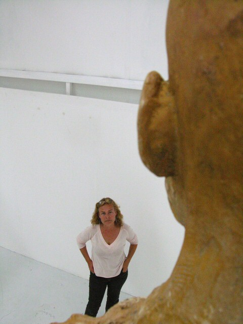 Sculptor looking up at a monumental sculpture in UCCA exhibition studio for MFA degree show