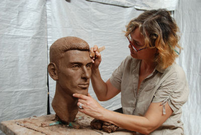 Sculptor Laury Dizengremel working on bust of Novak Djokovic