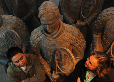 Sculptors Shen Xiaonan and Laury Dizengremel with Roger Federer sculpture and other tennis warrior statues